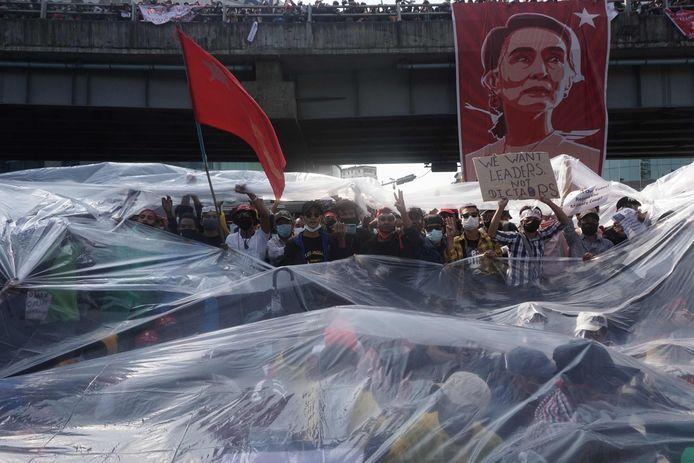 De betogers schuilen onder een enorm plastic zeil om het waterkanon te trotseren.