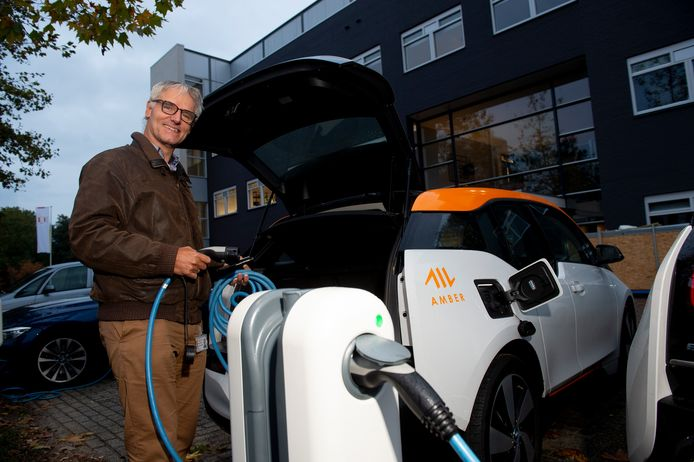 Oebele Korvemaker maakt gebruik van de elektrische deelauto Amber. Hier staat hij bij de auto op de Amberparkeerplaats aan de Waterloseweg in Apeldoorn, op korte fietsafstand van zijn woning.