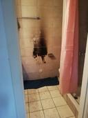 Het verwarmingselement hing aan deze zwartgeblakerde muur in de badkamer.