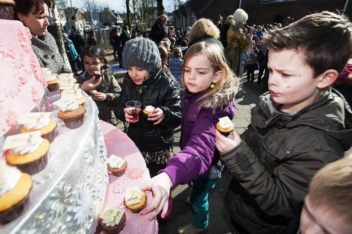 Leerlingen snoepen van cup cakes bij de opening.