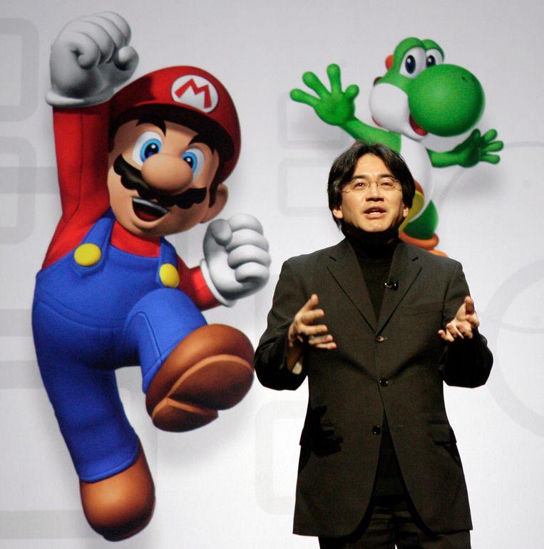 Satoru Iwata met in de achtergrond Nintendo's bekende figuren Mario en Yoshi. Beeld AP