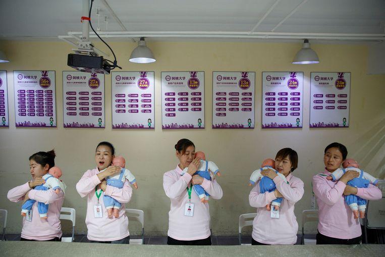 Studenten van de  Ayi Universiteit in Beijing (China) oefenen met babypoppen tijdens een cursus voor thuishulp.  Beeld Reuters