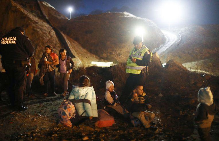 Een groep migranten wordt aan de grens door de Mexicaanse politie gecontroleerd en teruggestuurd naar een opvang, verder weg van de grens met de VS.  Beeld Getty Images