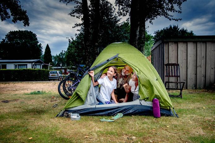 Campinggasten schuilen voor de regen in een tentje op Camping Betuwe in Kesteren.