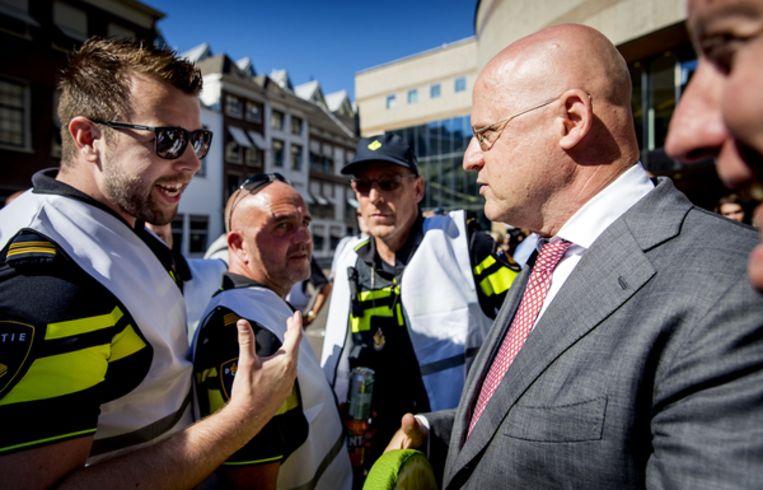 Ferdinand Grapperhaus in gesprek met politieagenten. Beeld ANP