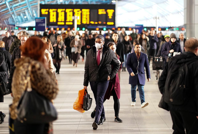 Een man met een gezichtsmasker op Waterloo station in London.