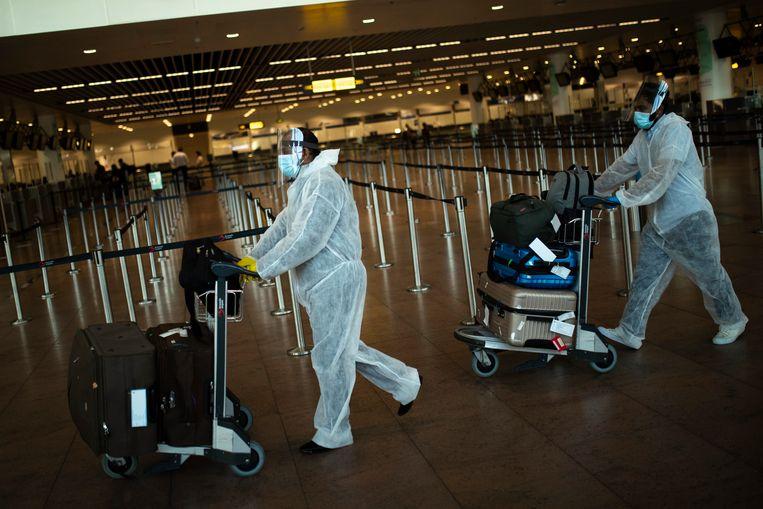 Eenzame reizigers in beschermende pakken op de luchthaven van Zaventem. Een 'vaccinpaspoort' is bedoeld om reizen weer mogelijk te maken. Beeld AP