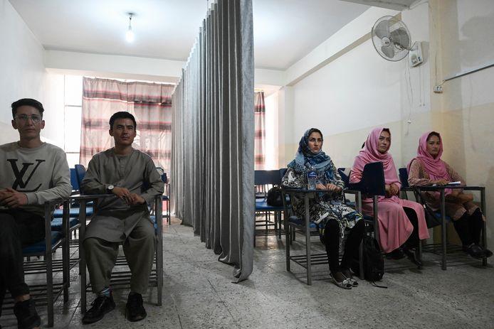 Mannelijke en vrouwelijke studenten op een universiteit in Kaboel worden door een gordijn gescheiden.