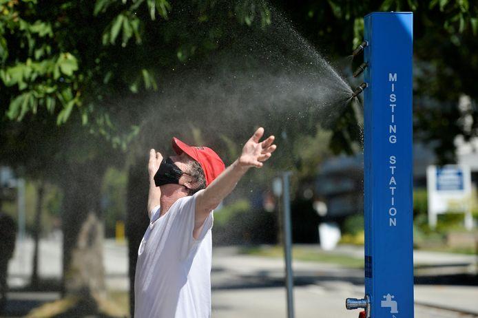 Een man zoekt verkoeling tijdens de hittegolf in Canada.