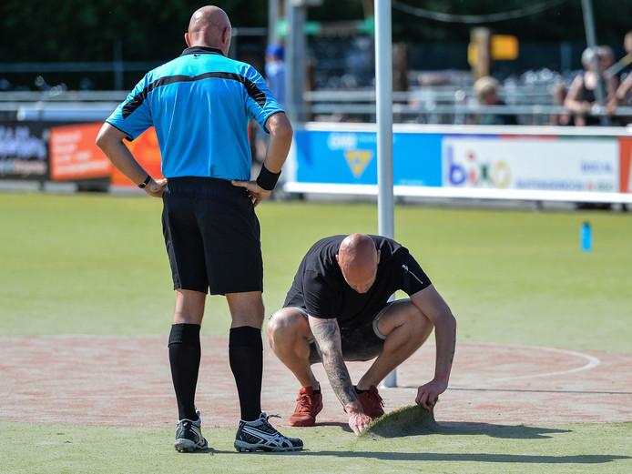 Elmar Hesselink, coach van KVZ , bekijkt in de slotfase van de laatste wedstrijd van het seizoen het stuk los gekomen kunstgras onder het toeziend oog van de scheidsrechter.