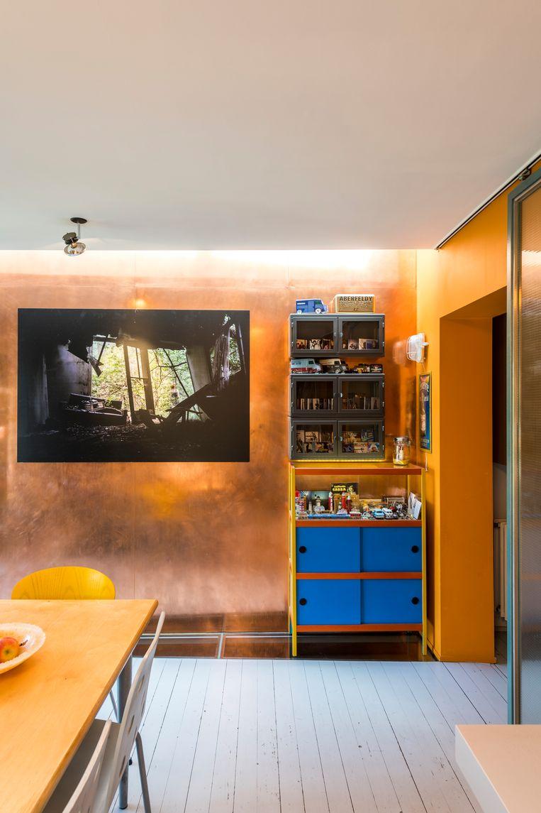 De met koper beklede accentmuur hult de eetkamer in een warme gloed.De kunstfoto van een verlaten boshuisje is een werk van visual artist Kristof Vranken.  Beeld Luc Roymans