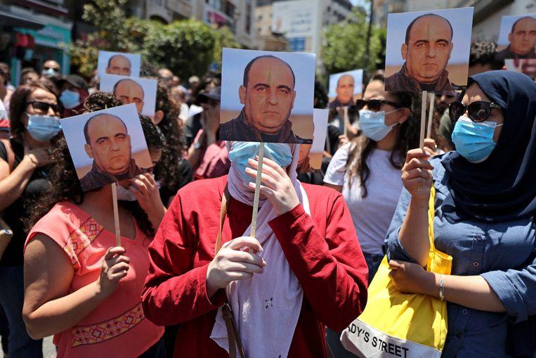 Demonstranten tegen de regering dragen portretten mee van de overleden Nizar Banat. Beeld AFP