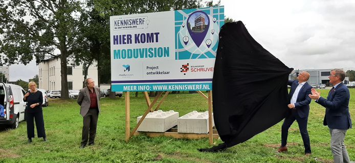 Jan-Dirk Marteijn van Bouwgroep Schrijvers trekt het laatste deel van het doek voor het bouwbord weg. Gerda van de Beek, Jan Willem Mol en wethouder John de Jonge (vlnr) kijken toe.