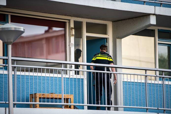 De politie treedt de woning binnen.