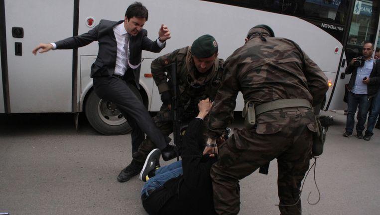 Een betoger wordt geschopt door Yusuf Yerkel, adviseur van Erdogan, terwijl agenten hem vasthouden tijdens een protest tegen het bezoek van Erdogan aan Soma. Beeld REUTERS