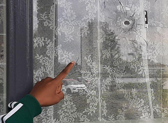 De 48-jarige bewoonster van een beschoten woning in Feijenoord wijst naar een van de kogelgaten in de ruit van haar woonkamer.