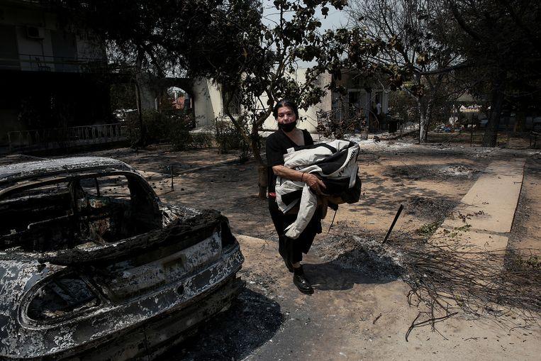 Een vrouw verlaat haar huis na een bosbrand in het gebied van Varybobi, een noordoostelijke voorstad van Athene. Beeld EPA