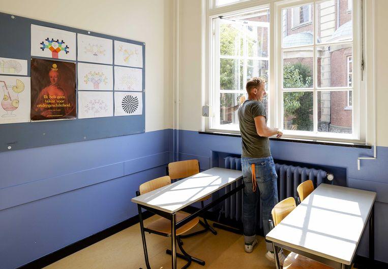 Een leraar van Atheneum College Hageveld in Heemstede zet de ramen open tijdens de voorbereidingen voor het begin van het nieuwe schooljaar. Beeld ANP
