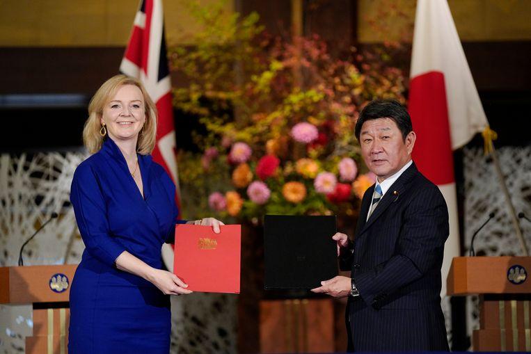 Brits minister van Internationale Handel Liz Truss tekent de deal met haar Japanse collega van Buitenlandse Zaken, Motegi Toshimitsu. Beeld AP