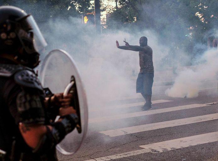 Een man die in Atlanta demonstreert tegen politiegeweld probeert in een wolk van traangas de politie tegen te houden. Volgens Amnesty International schond de politie hiermee op tal van plekkenmensenrechten.