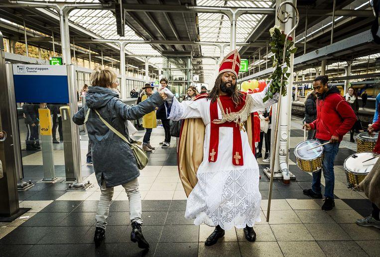 2016-11-05 11:58:13 AMSTERDAM - De Nieuwe Sint (Patrick Mathurin) danst met reizigers op een metrostation tijdens zijn intocht in Amsterdam. ANP REMKO DE WAAL Beeld ANP