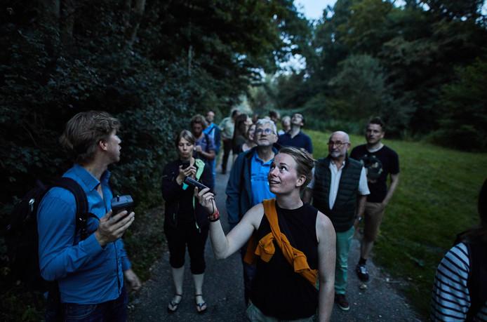 Deelnemers aan de excursie in het Kralingse Bos hopen het gezang van de rosse vleermuis op te vangen.