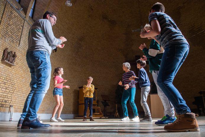 Dirigent Ruben de Grauw (links) en stemcoach Lucie HIllen (midden) geven zangles aan de kinderen in de Sacramentskerk.
