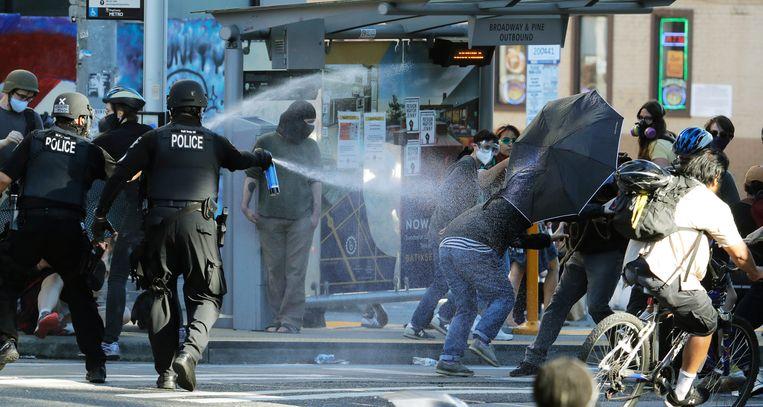 Politie spuit pepperspray op de demonstranten in Seattle. Beeld AP