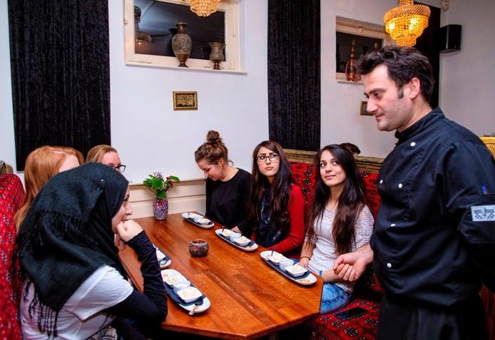 De eigenaar van Sarban geeft jonge dames uitleg over het dessert.