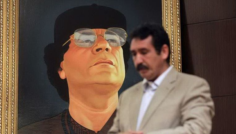 Een man bidt voor het portret van de Libische leider Kadafi in een hotel in Tripoli. © ap Beeld