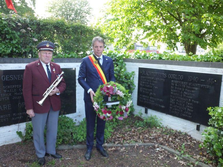Etienne Wandels en burgemeester Jan Vermeulen bij het oorlogsmonument in Petegem.