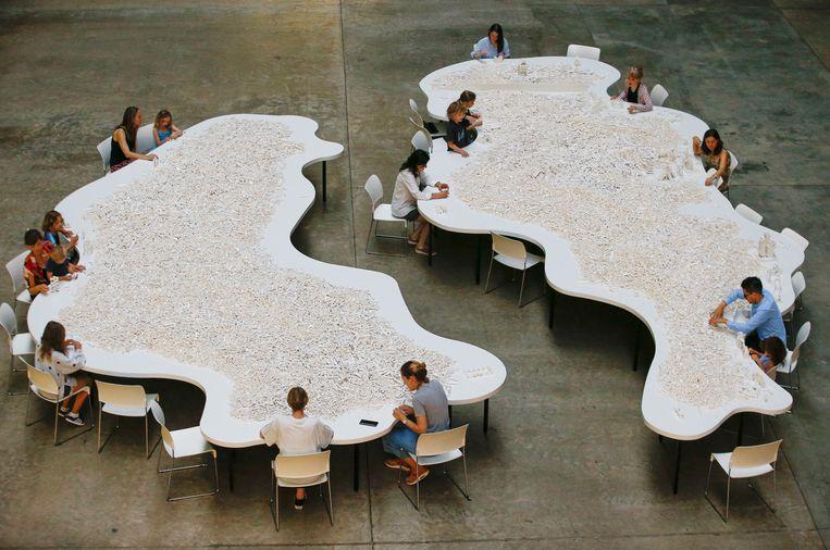 Bezoekers spelen in de Turbinehal van Tate Modern in Londen met de honderdduizend witte legosteentjes die deel uitmaken van 'The cubic structural evolution project' uit 2004 van Olafur Eliasson. In het museum is tot januari een overzichtstentoonstelling van de IJslands-Deense kunstenaar te zien. Beeld REUTERS