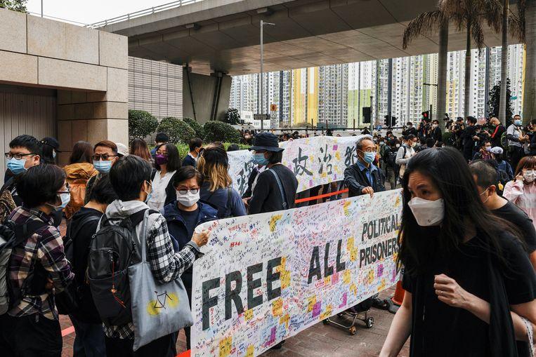 Aanhangers van de pro-democratie-activisten houden een banner op met de eis om alle politieke gevangenen vrij te laten in Hongkong. Beeld REUTERS