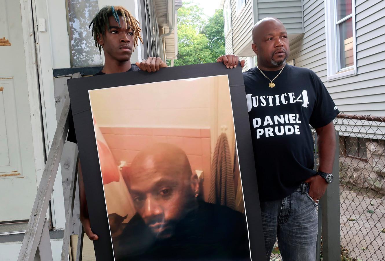 Joe en Armin Prude, een oom en neef van de overleden Daniel Prude, poseren bij zijn foto.