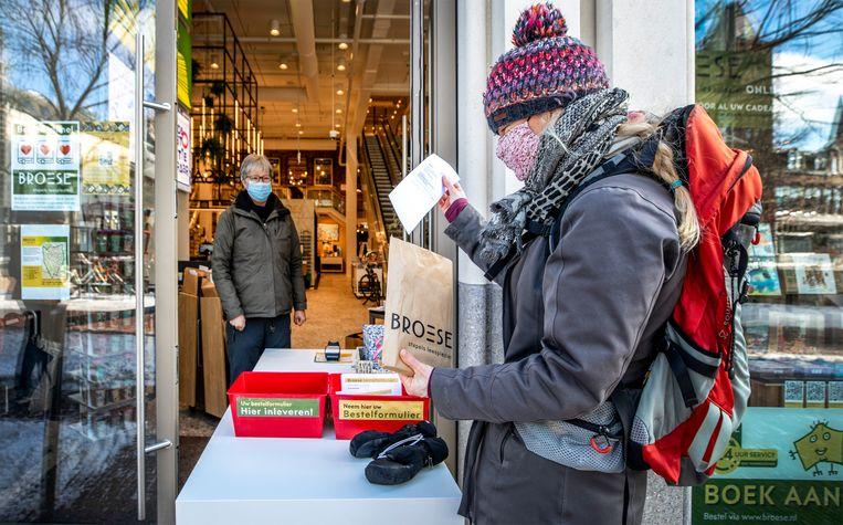 Een klant haalt een pakje af bij boekhandel Broese in hartje Utrecht. Binnen staat een medewerker die alle voorbijgangers begroet. Beeld Raymond Rutting / de Volkskrant