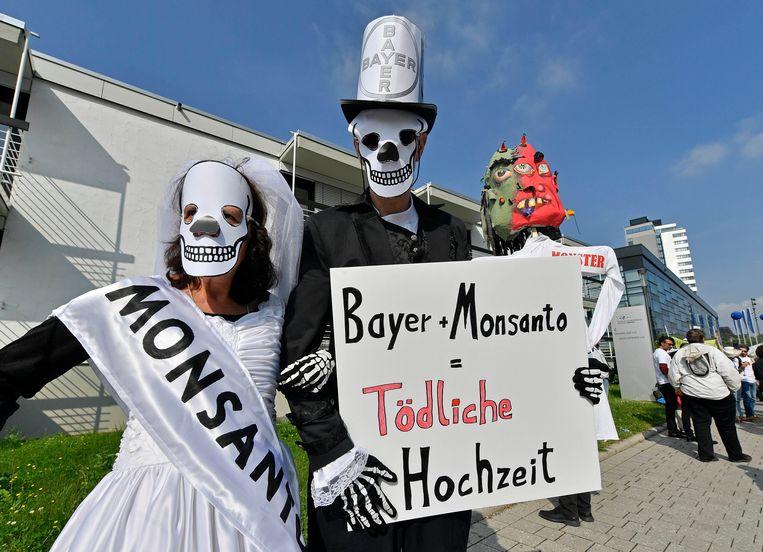 Demonstranten protesteren tegen de fusie met een bord dat zegt 'Bayer and Monsanto = Deadly Marriage'. Beeld AP