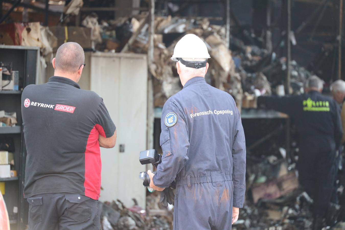 Forensische opsporings-medewerkers van de politie doen brandonderzoek bij het uitgebrande gebouw aan de Kapitein Rondairestraat in Tilburg.
