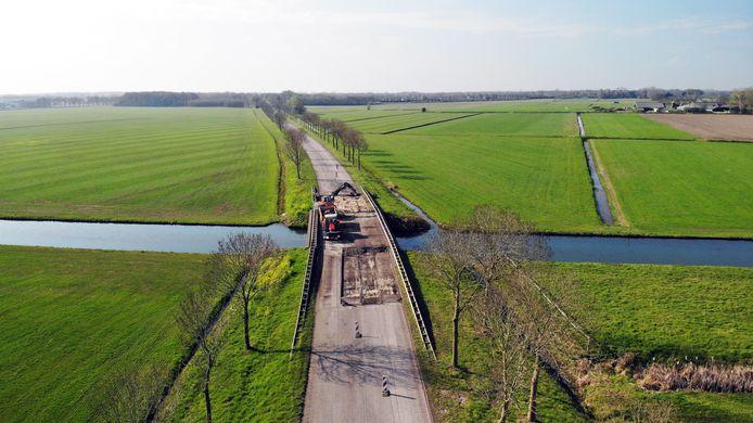 Een freesmachine verwijdert asfalt op de brug over de Nieuwe Wetering.
