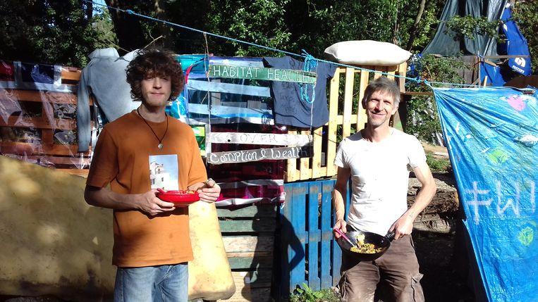 Latch en zijn zoon Seb bij het zelfgebouwde dorpje waar tientallen activisten in de bomen wonen. Beeld Patrick van IJzendoorn