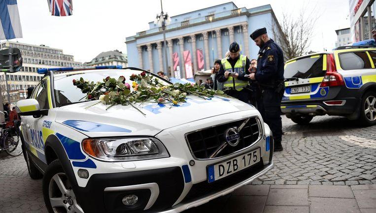Bloemen liggen op een politieauto in Stockholm. waar verslagen is gereageerd op de aanslag. Beeld epa