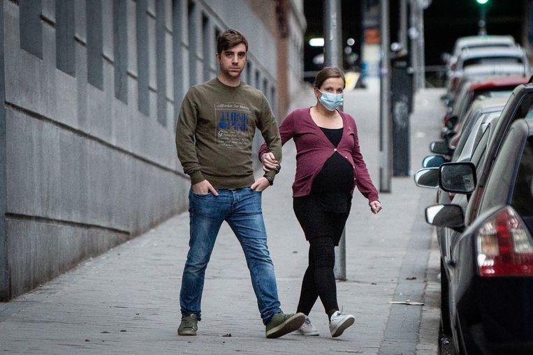 Een zwangere vrouw draagt een mondkapje in Madrid. De eerste onderzoeken duiden erop dat haar kind weinig gevaar loopt door het coronavirus. Beeld Getty Images