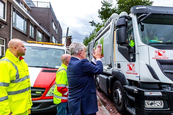 Burgemeester Jan van Zanen juicht een vuilniswagenchauffeur toe in zijn stad.