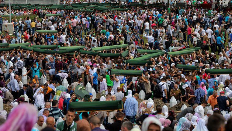 Bosniërs dragen 409 pas geïdentificeerde lichamen ten grave in Srebrenica, op 11 juli 2013. Beeld EPA
