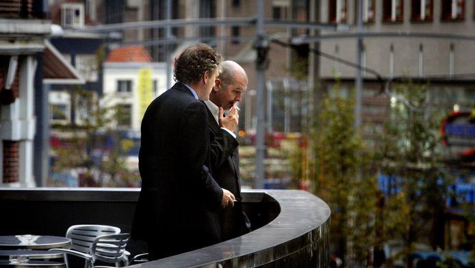 Politici Thom de Graaf en Jan Marijnissen roken op het balkon van de Tweede Kamer een sigaretje. In Duitsland kan dat verboden worden.