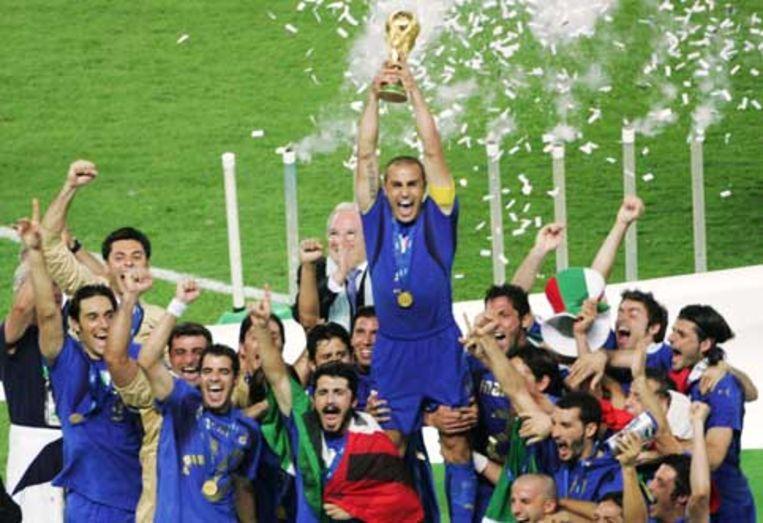 De Italiaanse aanvoerder Fabio Cannavaro houdt de wereldbeker omhoog, temidden van juichende teamgenoten. (AP) Beeld