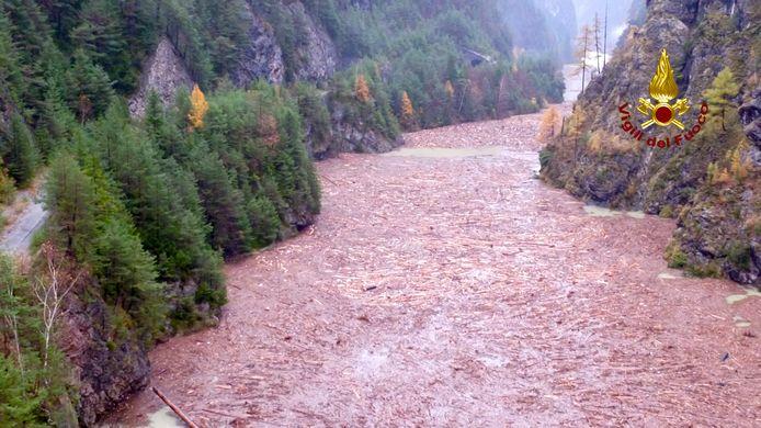Omgewaaide en geknapte bomen, modder en andere brokstokken als gevolg van de storm drijven naar het Comelico basin, in Val Visdende, in het noordoosten van Italië.