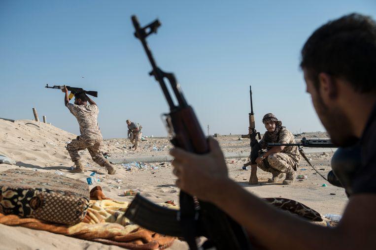Sirte, Libië, juni 2016. Soldaten van de Al-Marsa brigade bestoken vanaf een positie aan het strand van Sirte scherpschutters van IS.  Beeld Jeroen Oerlemans/De Beeldunie