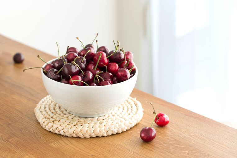 Fresh dark red cherry pile on wooden background. Close up image. Beeld Getty Images