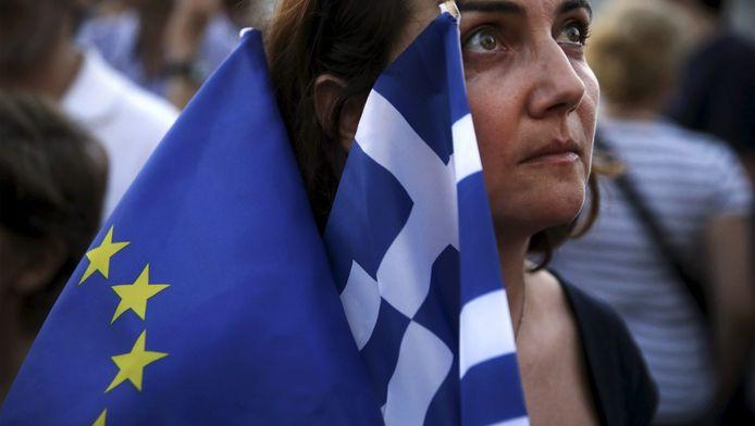 Een demonstrant in Athene met de Griekse en Europese vlag