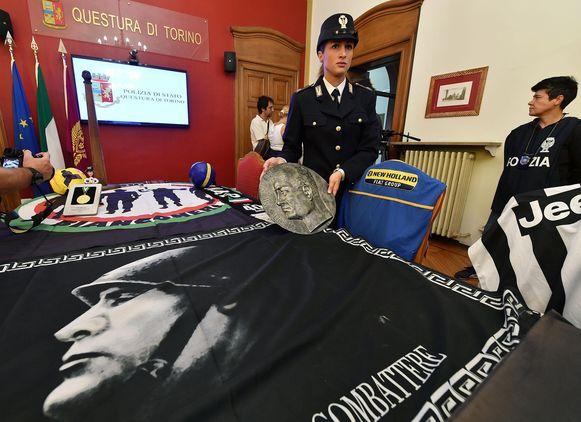 De politie toont tijdens de huiszoekingen gevonden objecten die leidden tot arrestaties van 12 'Ultras' van Juventus.